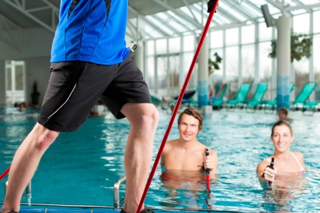 hydrotherapy: Fitness - a young couple - man and woman - doing sports and gymnastics or water aerobics under water in swimming pool or spa with Nordic walking sticks and trainer Stock Photo