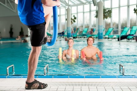 water aerobics: Fitness - a young couple - man and woman - doing sports and gymnastics or water aerobics under water in swimming pool or spa with swim noodle