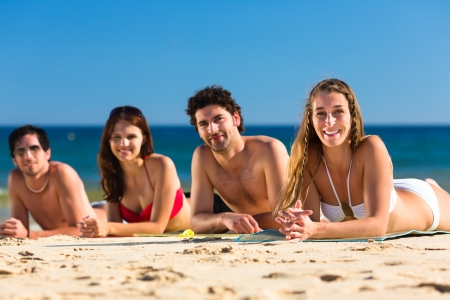 four friends: Group of Four friends - men and women - on the beach having lots of fun in their vacation