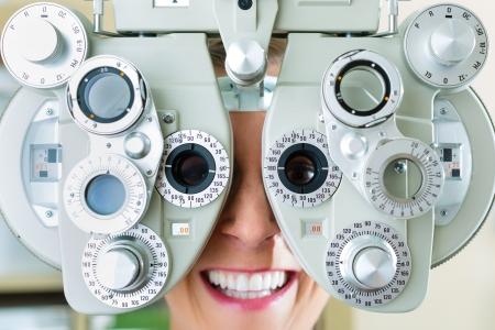 Jonge vrouw bij phoropter aan opticien of oogarts voor oogtest, ze is bijziend of verziend