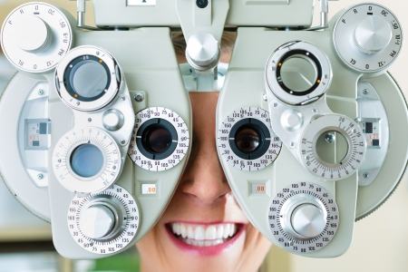pretty eyes: Young woman at phoropter at optician or ophthalmologist for eye test, she is near-sighted or long-sighted