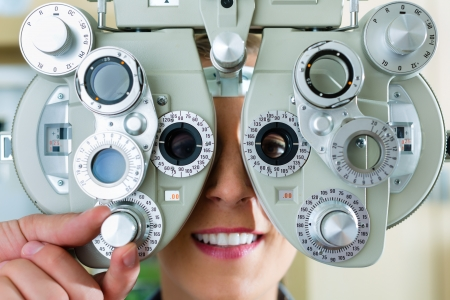 Young woman at phoropter at optician or ophthalmologist for eye test, she is near-sighted or long-sighted photo