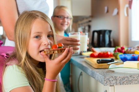 kids eating healthy: Family - mother making breakfast for her children in the morning and a snack for school