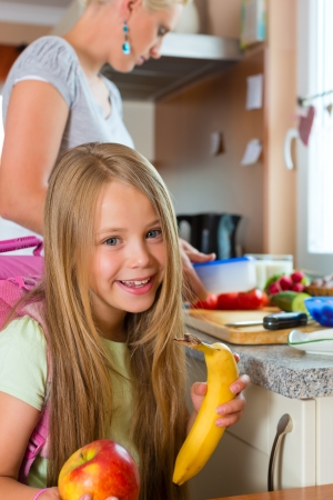 tupperware: Family - mother making breakfast for her children in the morning and a snack for school