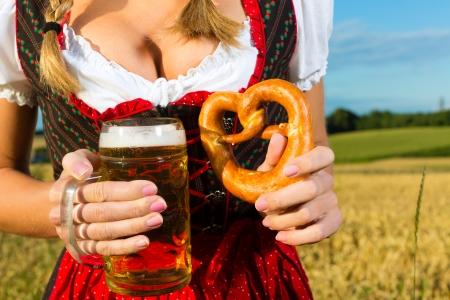 octoberfest: Joven mujer bávara beber cerveza y mantener un pretzel en dirndl en el prado