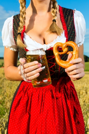 octoberfest: Joven mujer bebiendo cerveza bávara y mantener un pretzel en dirndl en el prado