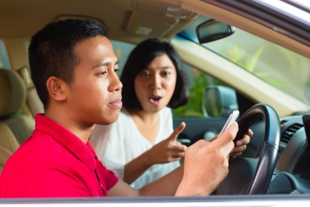 woman driving: Asian man texting message and asian woman scolding Stock Photo