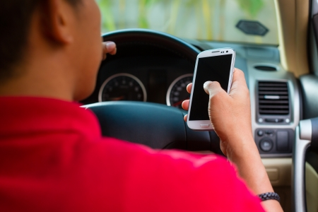 Asian man sitting in car with mobile phone in hand texting while driving photo