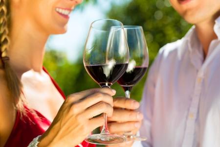 clinking: La mujer y el hombre en el vino tinto vi�a potable en el sol chocando las copas Foto de archivo