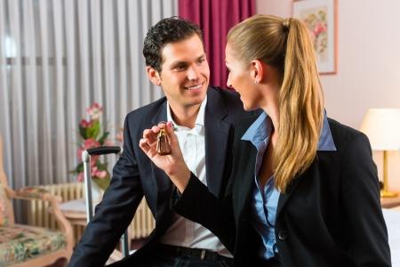 Young couple sitting on the bed in the hotel room and the woman has a key in her hand Stock Photo - 17620264