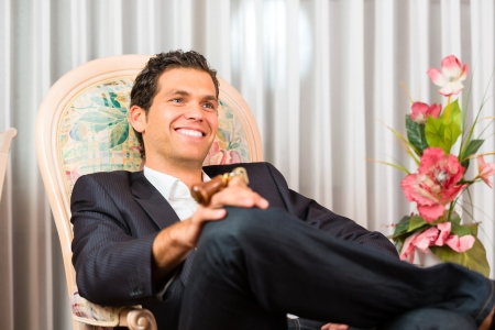 Young man sitting on the chair in the hotel room and is happy Stock Photo - 17620270