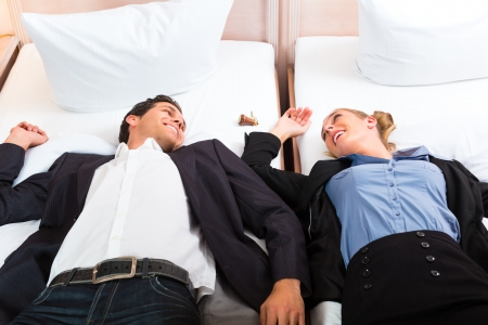 man in suite: Young couple lying on the bed in the hotel room und smiling