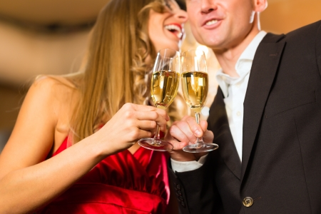 Couple, man and woman, drinking champagne in a fine dining restaurant, each with glass of sparkling wine in hand Stock Photo - 17620186
