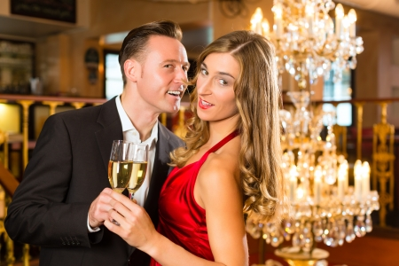 Couple, man and woman, drinking champagne in a fine dining restaurant, each with glass of sparkling wine in hand, a large chandelier is in Background Stock Photo - 17620183