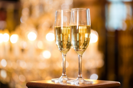 distinguished: Two glasses of champagne in a fine dining restaurant, a large chandelier is in Background Stock Photo