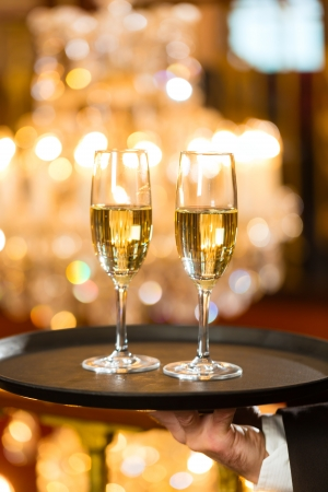 superiors: Waiter served champagne glasses on a tray in a fine dining restaurant, a large chandelier is in Background