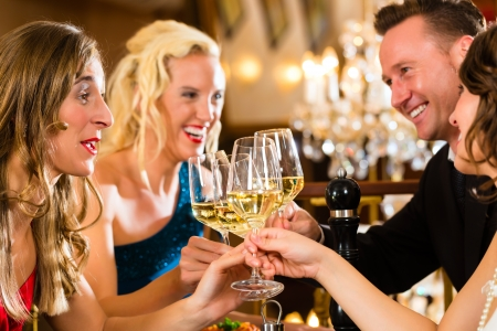 distinguished: Good friends for dinner or lunch in a fine restaurant, clinking glasses