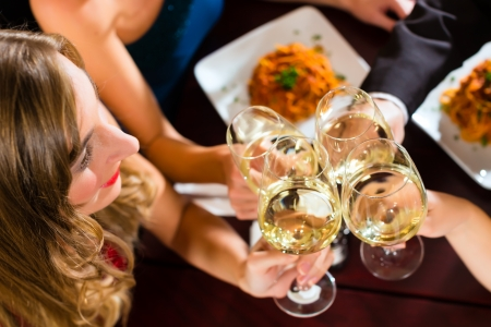 glass of white wine: Good friends for dinner or lunch in a fine restaurant, clinking glasses