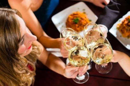 clinking: Los buenos amigos para la cena o el almuerzo en un restaurante de calidad, que tintinean los vidrios