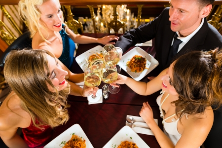 fine dining: Good friends for dinner or lunch in a fine restaurant, clinking glasses