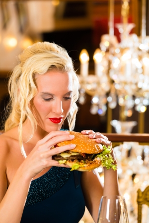 misbehave: Young woman in a fine dining restaurant eat a hamburger, she behaves improperly