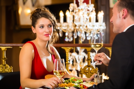 dinner date: happy couple have a romantic date in a fine dining restaurant, a large chandelier is in Background