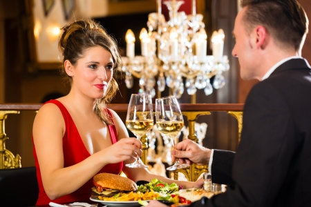 couple dining: happy couple have a romantic date in a fine dining restaurant, a large chandelier is in Background