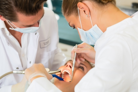 dentists: Female patient with dentist and assistant in a dental treatment, wearing masks and gloves