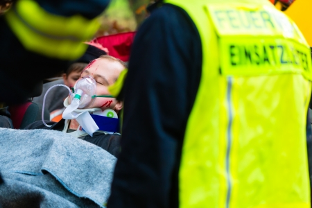 neck brace: Accident - Fire brigade and Rescue team pulling cart with wounded person wearing a neck brace and respirator Stock Photo