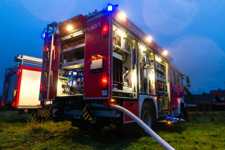 Fire truck or engine with flashing lights, lighting and hose in dusk, ready for deployment