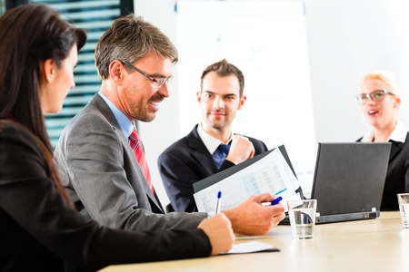 Business - businesspeople have a meeting with presentation in office, they negotiate a contract Stock Photo - 17620241