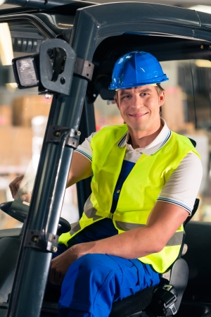 forklift driver in protective vest and forklift at warehouse of freight forwarding company, smiling Stock Photo - 17620189
