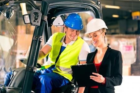forwarding: Carretilla elevadora visera del conductor y s�per femenino con el sujetapapeles en el almac�n de la empresa de transporte de carga Foto de archivo