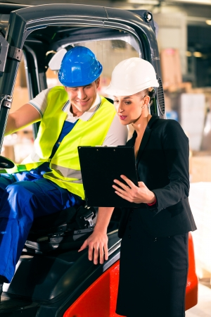Forklift driver and female super visor with clipboard at warehouse of freight forwarding company Stock Photo - 17620217