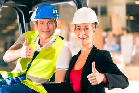 forwarding: Carretilla elevadora visera del conductor y s�per femenino con el sujetapapeles en el almac�n de la empresa de transporte de carga - pulgares para arriba