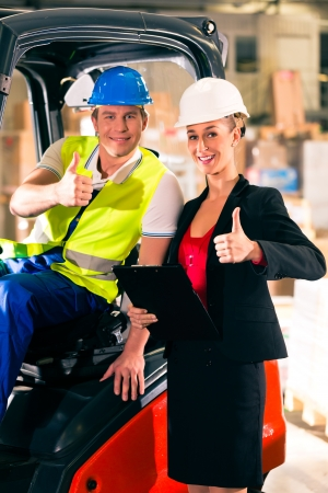shipper: Forklift driver and female super visor with clipboard at warehouse of freight forwarding company - thumbs up