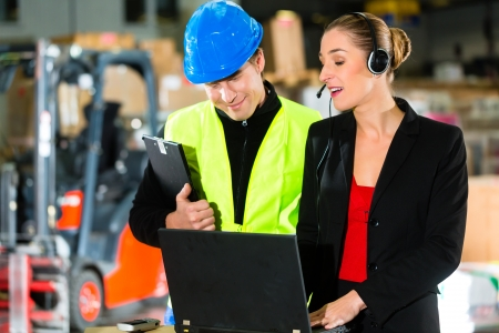 warehouseman: Teamwork - warehouseman or forklift driver and female supervisor with laptop, headset and cell phone, at warehouse of freight forwarding company - a forklift is in Background