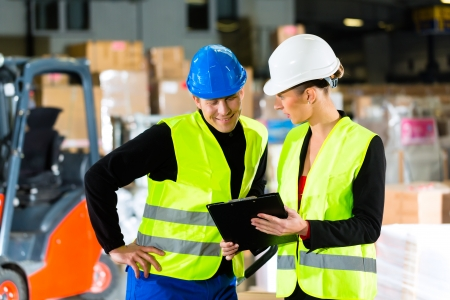Worker or warehouseman and his coworker with clipboard at warehouse of freight forwarding company, pointing photo