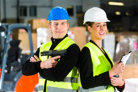 Teamwork- Worker or warehouseman with scanner and his coworker with clipboard at warehouse of freight forwarding company photo