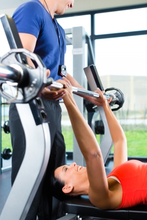 personal trainer woman: Woman with her personal fitness trainer in the gym exercising with dumbbells, she is using barbell on a weight bench