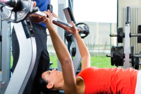 Woman with her personal fitness trainer in the gym exercising with dumbbells, she is using barbell on a weight bench photo