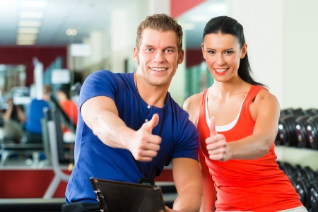 trainer: Woman with her personal fitness trainer in the gym exercising with dumbbells