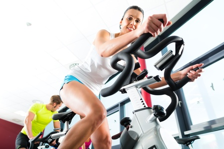 fitness equipment: Young People - group of women and men - doing sport Spinning in the gym for fitness