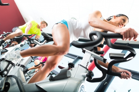 fitness instructor: Young People - group of women and men - doing sport Spinning in the gym for fitness