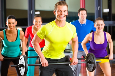 sports coach: group of young sport people training with barbell at a gym for better fitness
