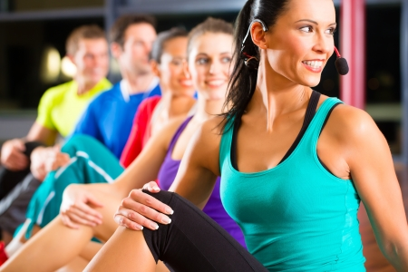 Group of young people stretching in gym for better fitness led by instructor photo
