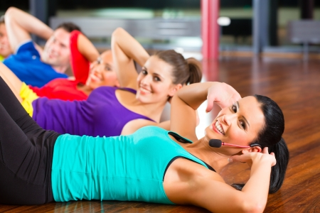 abdominal: Fitness group with instructor in gym doing stomach crunches for sport Stock Photo