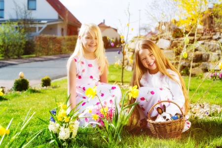 easter basket: Children on an Easter Egg hunt on a meadow in spring, a living Easter Bunny is sitting in the Easter basket