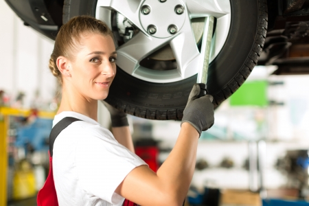 bluey: Young woman as female car mechanic working on an auto in workstation