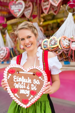 dirndl: Young woman in traditional Bavarian clothes - dirndl or tracht -with a gingerbread souvenir heart on a festival or Oktoberfest